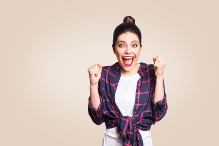 surprised portrait of happy winner ecstatic young woman with casual style having shocked look, exclaiming, keeping mouth wide open and fists clenched while celebrating success.