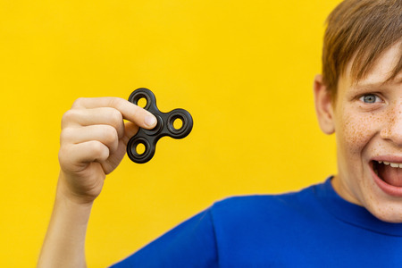 Young beautiful happy boy with freckles blue t-shirt holding fidget spinner on yellow background with amazed face.