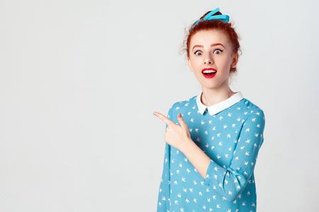 髪の結び目横に彼女の人差し指を指している、眉を高め、口を大きく開くと、グレー コピー スペースの壁に何か驚くべきことを示すを維持する赤毛