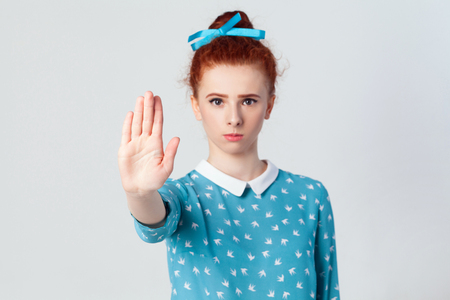 Stop! begative emotions, feelings, body language. Isolated studio shot on gray background. Young annoyed redhead girl with bad attitude making stop gesture with her palm outward, saying no, expressing denial or restriction. Focus on hand.