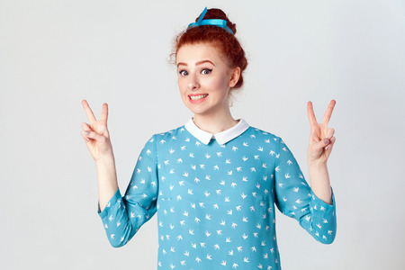 Young beautiful redhead girl with blue dress and head band showing peace sign. Isolated studio shot on gray background.