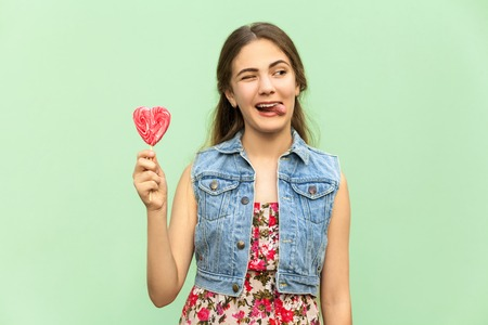 blue green background: Young teenage girl with blondie long hair, wink at camera, tongue out, holds lolipop, having funny look. Isolated studio shot on light green background.