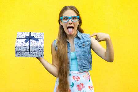 The funny blonde girl in dress and blue glasses, tongue out at the camera, pointing finger on present box, isolated over yellow background. Indoor studio shoot Stock Photo