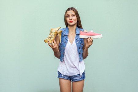 uninterested: The beautiful caucasian casual girl with freckles got choosing comfortable sneakers or inconvenient but handsome high heel, thinking and looking at camera. Isolated studio shot on light green background