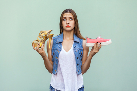 Pretty casual style girl with freckles got choosing sneakers or inconvenient but handsome shoes, and thinking. Isolated studio shot on light green background Zdjęcie Seryjne