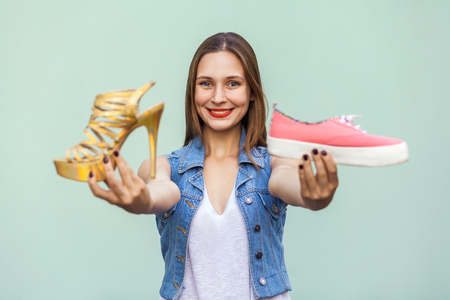 uninterested: The tender and cute teenage girl with freckles got choosing in shop sneakers or inconvenient but handsome shoes, looking at camera with toothy smile. Isolated studio shot on light green background Stock Photo