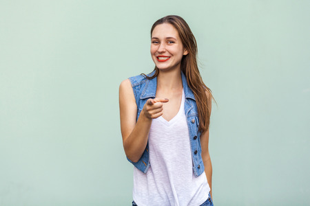 Funny freckled girl in casual white t shirt and jeans jecket, pointing finger at camera and toothy smile. Isolated studio shot on light green background