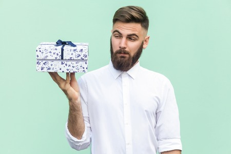 Hmm what is it! Bearded man looking at gift box and want too open. Light green background. Studio shot Stock Photo