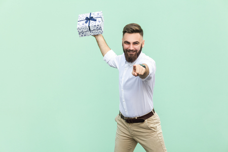 Its for you! Young adult businessman, holding gift box, pointing finger at camera and toothy smile. Isolated on light green background. Indoor, studio shot