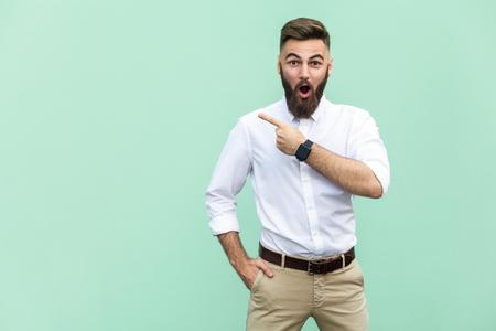 うわー!ショックでひげとハンサムな若い成人男性。明るい緑の背景に分離されて立っている間指す