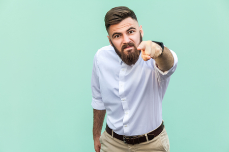 Angry bearded businessman with white shirt looking at camera and pointing finger to you. Studio shot isolated on light green background. Stock fotó