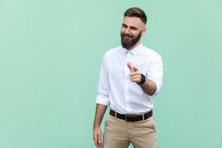 Hey you! Young adult bearded man, pointing finger and looking at camera. On light green background. Indoor, studio shot