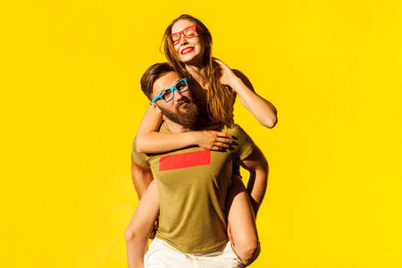 Piggyback. Happiness friend looking at camera and posing on yellow background. Studio shot