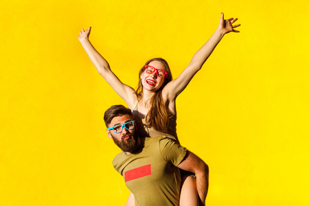 Young adult bearded man grimacing at camera. Freckled cute brunette hands up and shout. Yellow background, studio shot