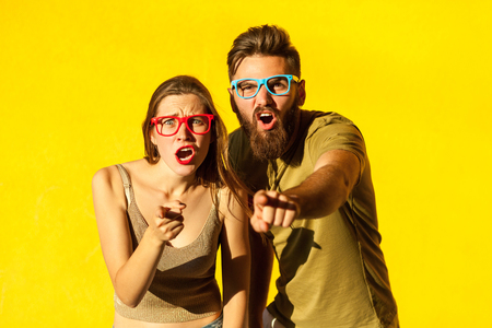 Hey you! Young adult bearded man, and cute brunette pointing fingers and looking at camera. On yellow background. Indoor, studio shot