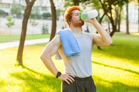 Young adult redhead and freckles man, drink water after cross and closed eyes. Outdoor