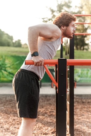 Pull ups in horizontal bars. Young adult bearded redhead man doing pull ups. Outdoor Stock Photo