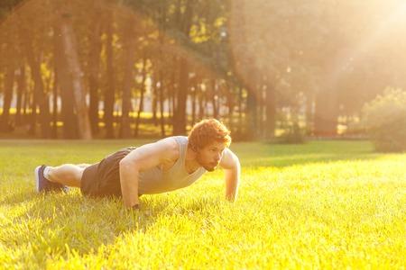 Push ups. Sunny. Summer. Redhead and bearded fitness model doing push ups. Outdoor