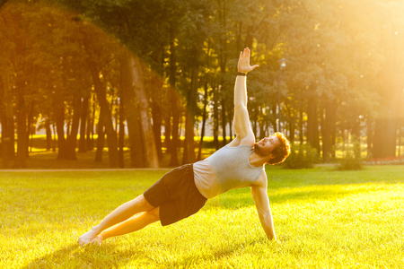 staying fit: Strong young adult man doing yoga. Stay in plank on one arm. Looking up to the sky. Outdoor shot