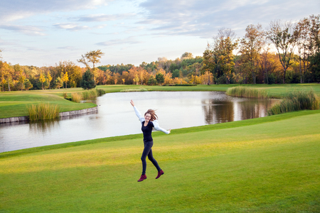 Cute girl jumping and running on the green grass of the golf course. Outdoor shot, autumn. Good sunny day Stock Photo