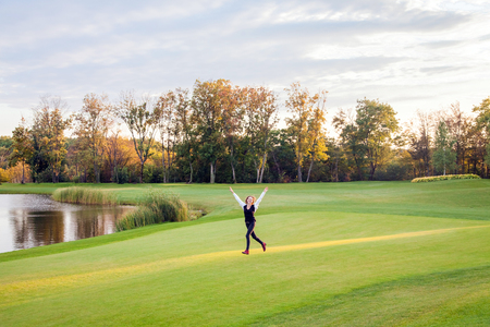 Girl runs on the green grass of the golf course. The girl happiness. Outdoor shot Imagens