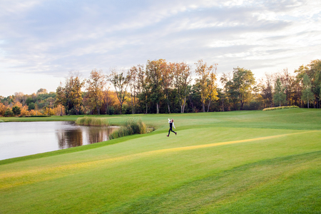 Autumn, lake, golf course. Young adult girl running on the green grass of the golf course. The girl freedom. Outdoor Stock Photo