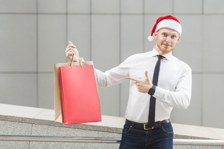 Black friday in winter. Happiness red head businessman in santa hat , holding shopping bags on hands, pointing fingers and looking at camera. Outdoor shoot, gray wall