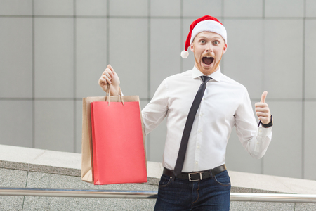Winter sales and shopping. Young adult ginger businessman thumbs up and looking at camera with shocked face. Outdoor Stock Photo