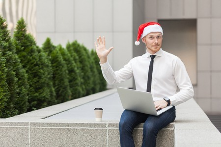 hi hat: Well hi! Happiness businessman in santa hat, looking at camera and send hello sign. Christmas concept, winter
