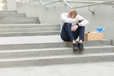 Unhappy red hair and bearded business man siting with cardboard, holing head and feeling sad and cry. Outdoor