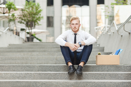 Unfair ginger worker sit on stair and seriosly looking at camera. Outdoor