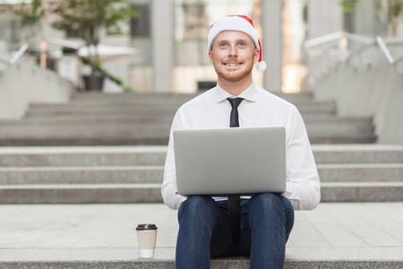 Imagination and dreaming concept. Young adult businessman working outsourcing, wondering and toothy smile. Outdoor Stock Photo