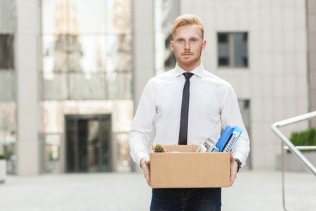 Youre fired. Unhappy bearded business man going out with cardboard, looking at camera and feeling looser. Outdoor