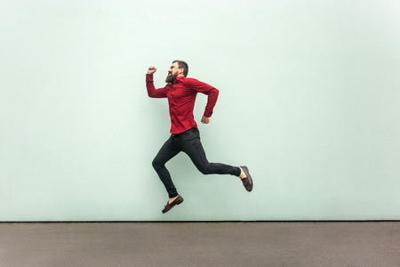 Profile happiness jumping man in red shirt with beard and mustache, casual style. Outdoor, gray wall 版權商用圖片