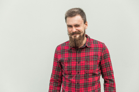 Flirt and wink. Carefree bearded man winked at camera and smiling. Studio shot, gray background