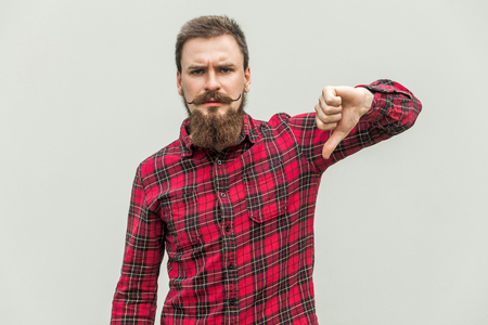 disapprove: Handsome bearded man showing thumbs down sign to dislike, isolated on gray background Stock Photo