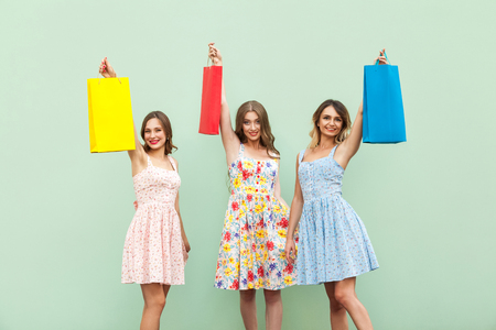 Young adult girl in dress, showing her bags after shopping. Hands up and holding her colorful bags. looking at camera and smiling. Isolated on green background. Studio shot