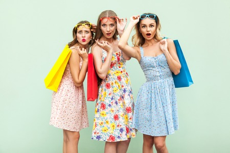 Three wonder girls with packages and new clothes. In shocked from black friday. Looking at camera and amazed. Studio shot. Green background Stock Photo
