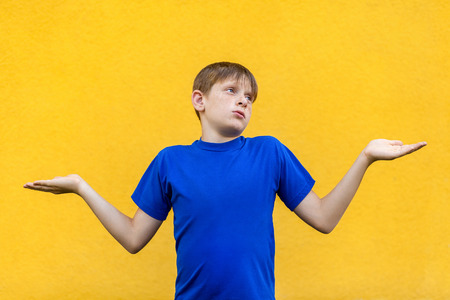 I dont know. Confused young freckled boy. Studio shot, isolated on yellow background