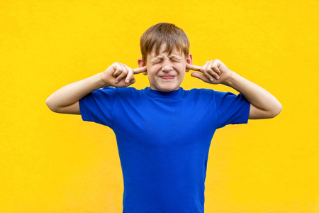 I dont want  hear  you! Sadness ginger boy holding fingers on ears and   closed eyes. Isolated on yellow background Stock Photo