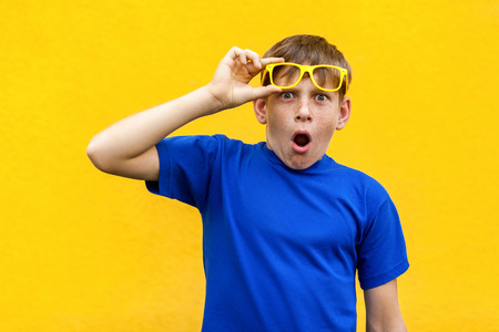 Funny boy in color glasses looking at camera and shocked. Isolated on yellow background , indoor studio shot