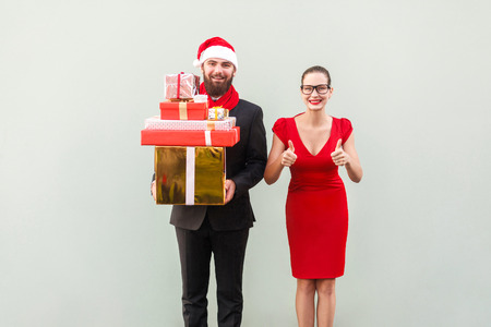Christmas, gifts concept. Bearded businessman holding many gift box for family, her woman thumbs up and smiling. Happiness well dressed  couple looking at camera and toothy smiling. Studio shot