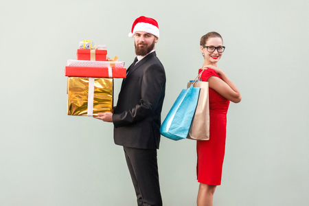 Back to back. Profile view man in red hat and woman in red dress and glasses. Happiness couple holding christmas gifts and colorful packages and looking at camera with toothy smiling. Studio shot