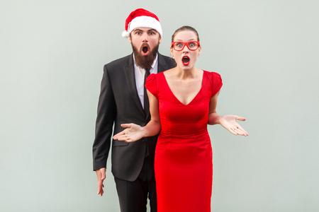 Empresario y mujer mirando a cámara, de pie juntos, abrir la boca con la cara sorprendida. Estudio, tiro, fondo gris Foto de archivo