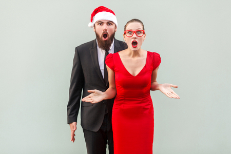 Businessman and woman looking at camera, standing together, open mouth with amazed face. Studio shot, gray background