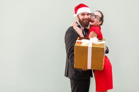 gave: Close up. Love concept. Beautiful girl hugging happy businessman, because he gave a  gifts. Studio shot, gray background