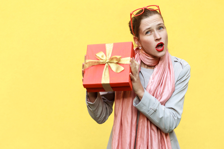 Cant stand, Its my! Playfully young adult  girl holding gift box. Isolated on yellow background, studio shot Stock Photo