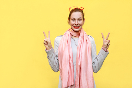 Young beautiful redhead woman showing peace sign. Isolated studio shot on yellow background. Stock Photo