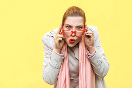 Redhead woman wearing coat, opening mouths widely, having surprised shocked looks.  Studio shot, isolated on yellow wall Stockfoto