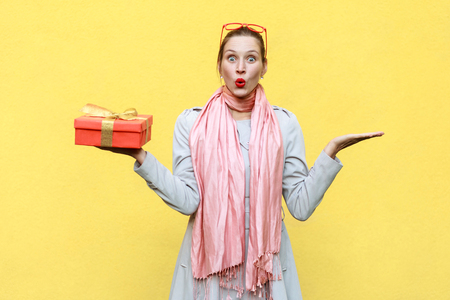 Hand on sides and holding christmas box. Woman looking at camera with shocked face and open mouth. Studio shot, isolated on yellow wall